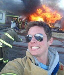 شاب يلتقط سيلفي وهو يضحك أثناء إخماد رجال الدفاع المدني في الولايات لحريق شب في أحد الأماكن